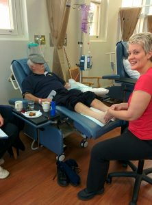 Andrea providing foot massage to a patient receiving chemotherapy